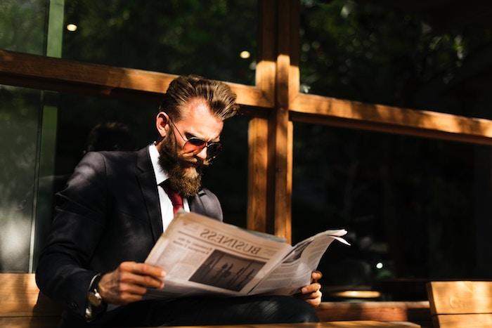 smoking homme, chemise blanche avec cravate bordeaux, homme avec journal dans la rue