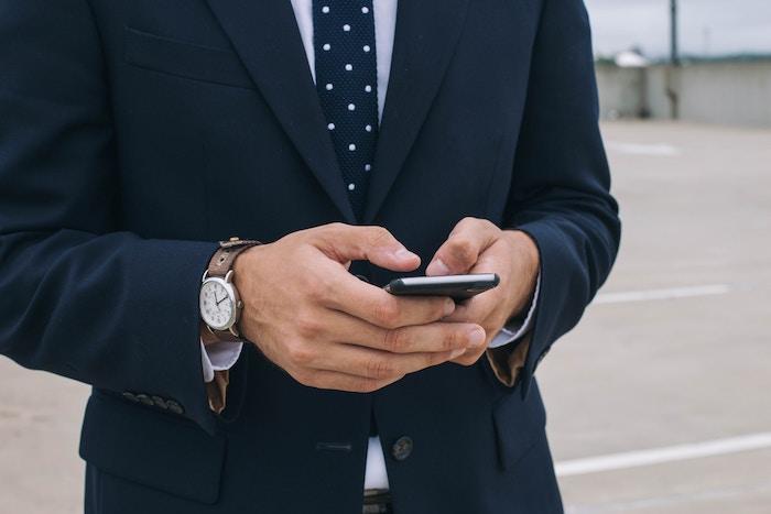 look businessman en costume bleu foncé, chemise blanche avec cravate bleu foncé et montre en marron