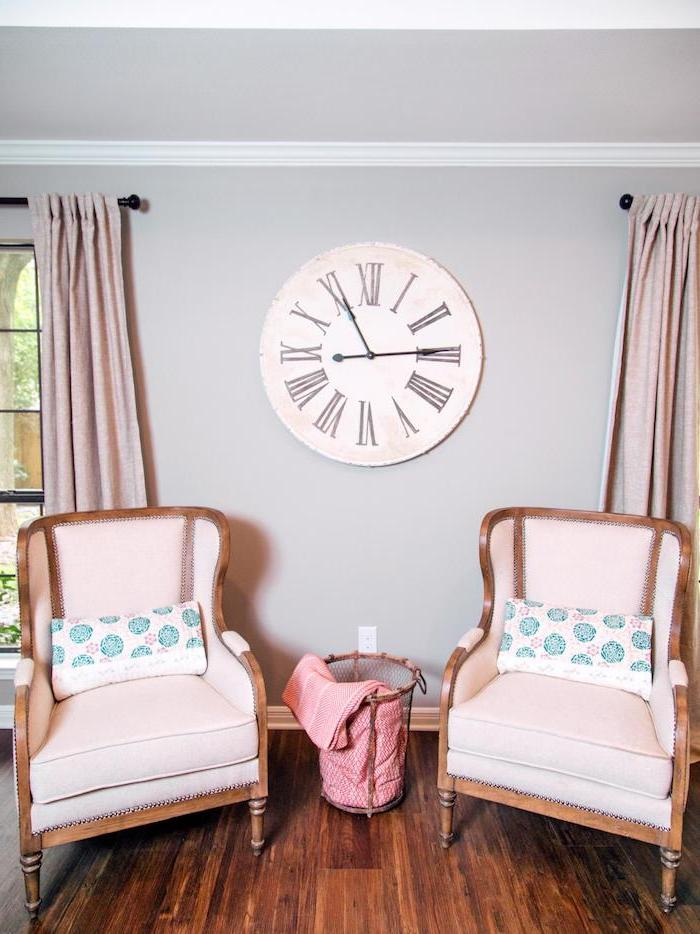chambre à coucher aux murs ivoire, fauteuils anciens en tissu rose pale, grande fenêtre à carreaux noirs