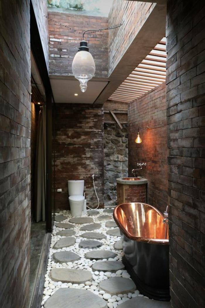 idées déco salle de bain, sol en pierres et galets, baignoire cuivrée, murs en briques