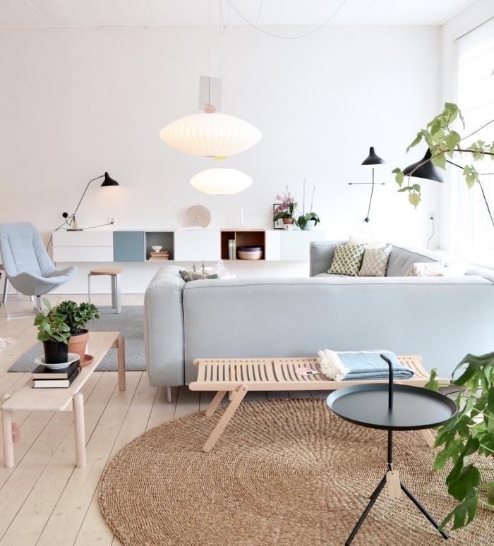 amenagement salon moderne avec canapé gris, tapis scandinave gris et autre tapis rond marron, canapé d angle gris clair, parquet clair, mobilier scandinave en bois, meuble tv blanc