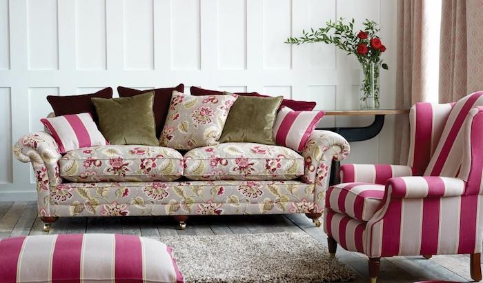 amenagement salon moderne, fauteuil et rabouret blanc et rose framboise, tapis gris, canapé gris imprimé floral, coussins vert, bordeau et framboise