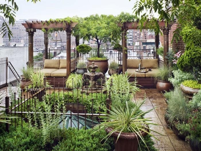 amenagement terrasse fleurie, idée fauteuils en bois avec ombrage, tonnelle, fontaine au centre, carrelage, plusieurs arbres et arbsutes vertes