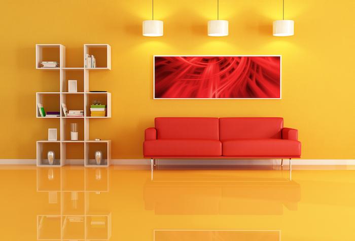 canapé rouge dans un salon jaune, étagère en bois, mur et sol jaune, suspensions blanches, deco salon design simple