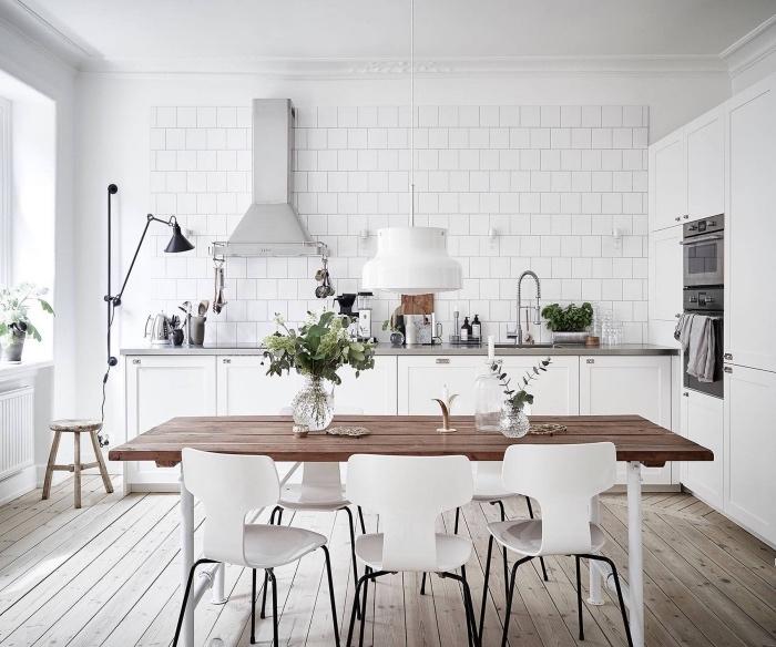 deco cuisine scandinave, façade cuisine et carrelage blanc, table salle à manger bois brut et chaises blanches scandinaves, parquet clair bois, plan de travail inox