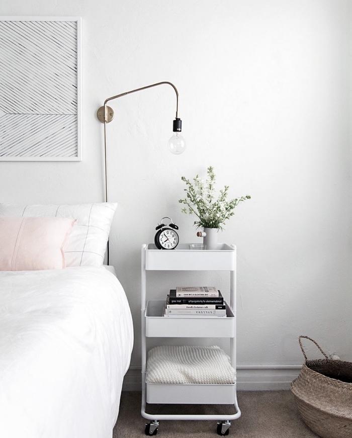 idee amengement chambre scandinave en blanc, avec coussin rose et table de nuit blanche à roulettes avec des étagères, tapis gris