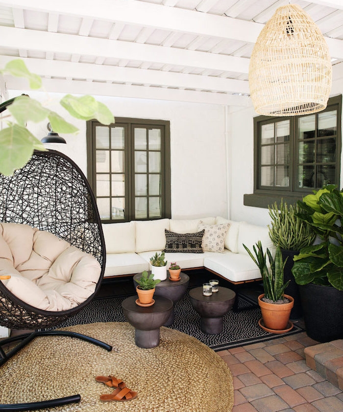 idee salon de jardin oriental avec canapé en bois et métal et coussins d assise blancs, tapis noir et marron, fauteuil noir design intéressant, suspension originale et plantes vertes
