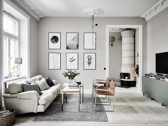 amenagement salon scandinave, couleur mur et canap;e gris, chaises marron, tapis gris, tables basses, meuble tv vert pastel, deco murale graphique