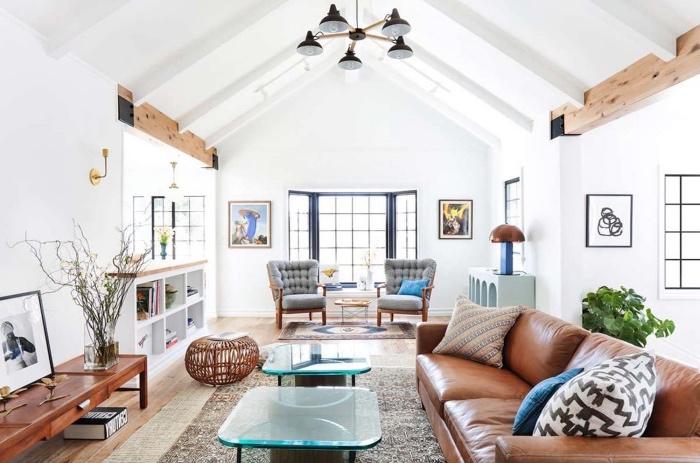 modele salon scandinave, canapé en cuir, tables basses en verre et metal, meuble tv bois, tapis scandinave gris, fauteuils bois avec coussins gris, poutres apparentes rustiques