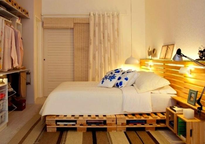 idée comemnt fabriquer un lit en palette avec une tête de lit en palette, matelas blanc, linge de lit blanc et coussins blancs à motifs de fleurs bleues, deco recup simple