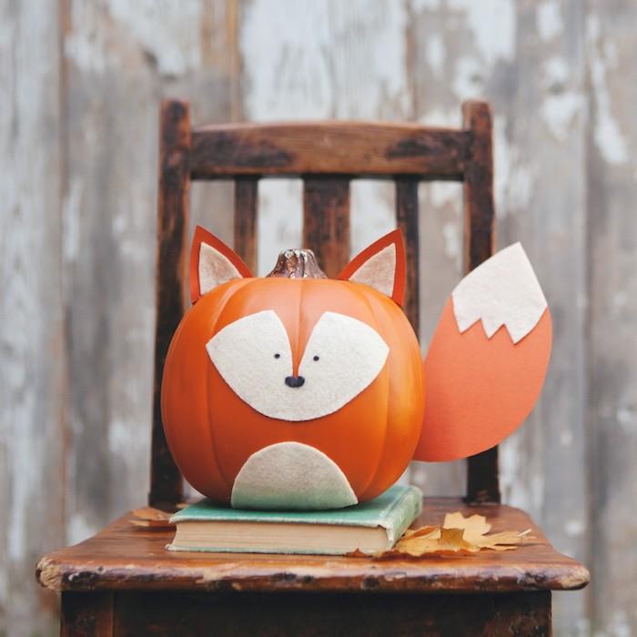 un renard fabriqué à partir une citrouille orange, feutrine et papier pour visage, ventre, queue et oreilles, bricolage automne