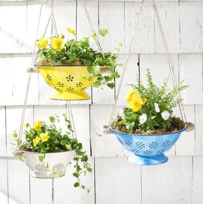 projet de bricolage facile printemps pour fabriquer une jardinière suspendue à partir une passoire avec des fleur plantées dedans