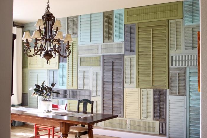 décoration murale de volets de fenêtres de tailles différentes, repeints en gris, vert pistache, jaune bleu pastel, idée créative récup