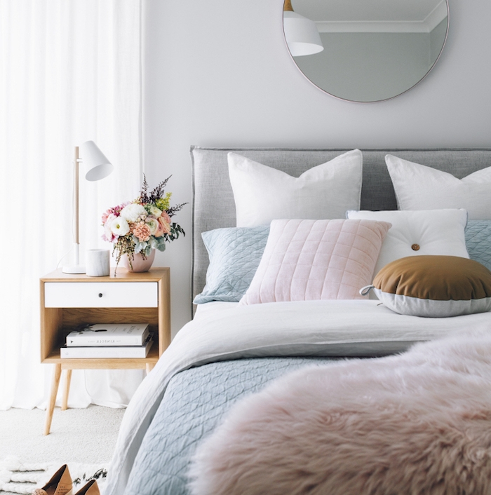 decoration de chambre cocoooning, linge de lit blanc, rose et bleu pastel, table de nuit en bois, bouquet de fleurs, tapis gris clair