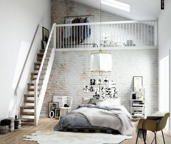 idée déco chambre cocooning, tapis peau animal, mur en briques, lit en palette avec linge de lit gris et blanc, parquet clair, suspension originale, mur de photographies noir et blanc