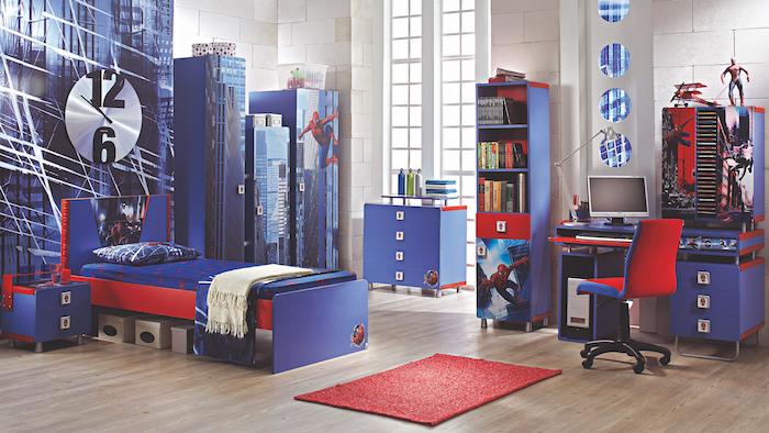 idée deco chambre enfant garcon, parquet clair, tapis rouge mobilier bleu marine avec des accents rouges, mur blanc cassé, décoration thématique chambre spiderman, bleu et rouge