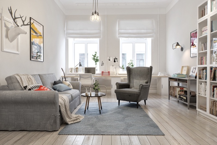 déco scandinave dans un salon, canapé, fauteuil et tapis gris, parquet clair, coin bureau avec chaise et bureau blanc, bibliothèque blanche, trophée de chasse