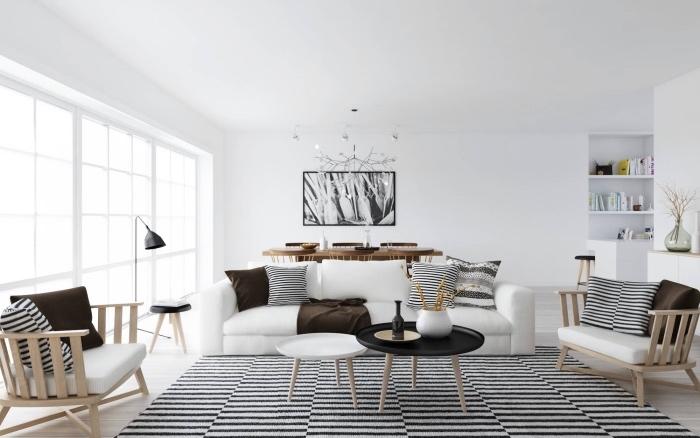 salon moderne dans une maison scandinave, tapis noir et blanc, canapé blanc, fauteuils nbois avec coussins d assise blancs, coussins decoratifs noir et blanc et marron, chaises et table en bois et decoration murale peinture graphique