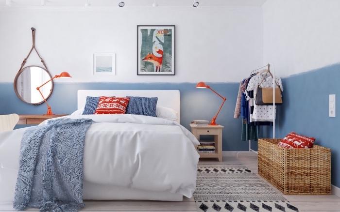 chambre à coucher dans une maison scandinave, meuble scandinave lit blanc, linge de lit blanc, bleu et rouge, decoration murale bleu et blanc, miroir rond, tapis noir et blanc, deco murale dessin renard dans un fôret