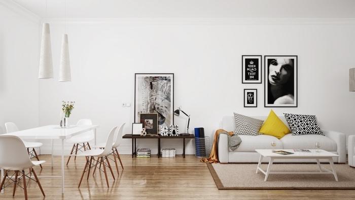 déco salon salle à manger dans une maison scandinave, parquet clair, canapé blanc, coussin jaune, noir et blanc, table basse blanche, coin repas table et chaises blanches, deco graphique