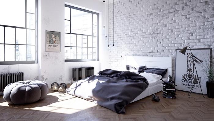 déco scandinave industrielle, murs en briques blanchis, linge de lit blanc et gris, parquet clair, pouf gris, suspensions industrielles, decoration graphique