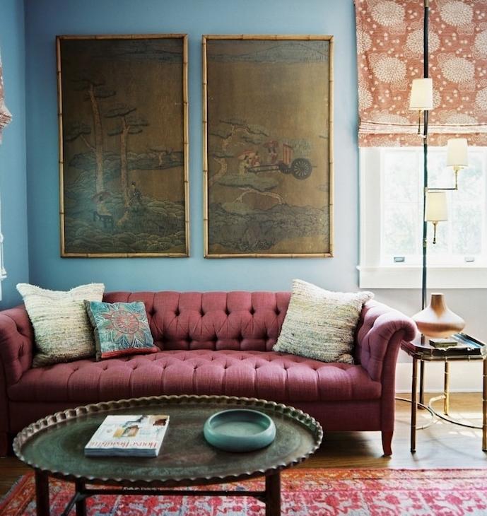 canapé couleur bordeau dans une chambre bleu, tapis oriental usé table basse vintage en métal, panneaux décoratifs japonais