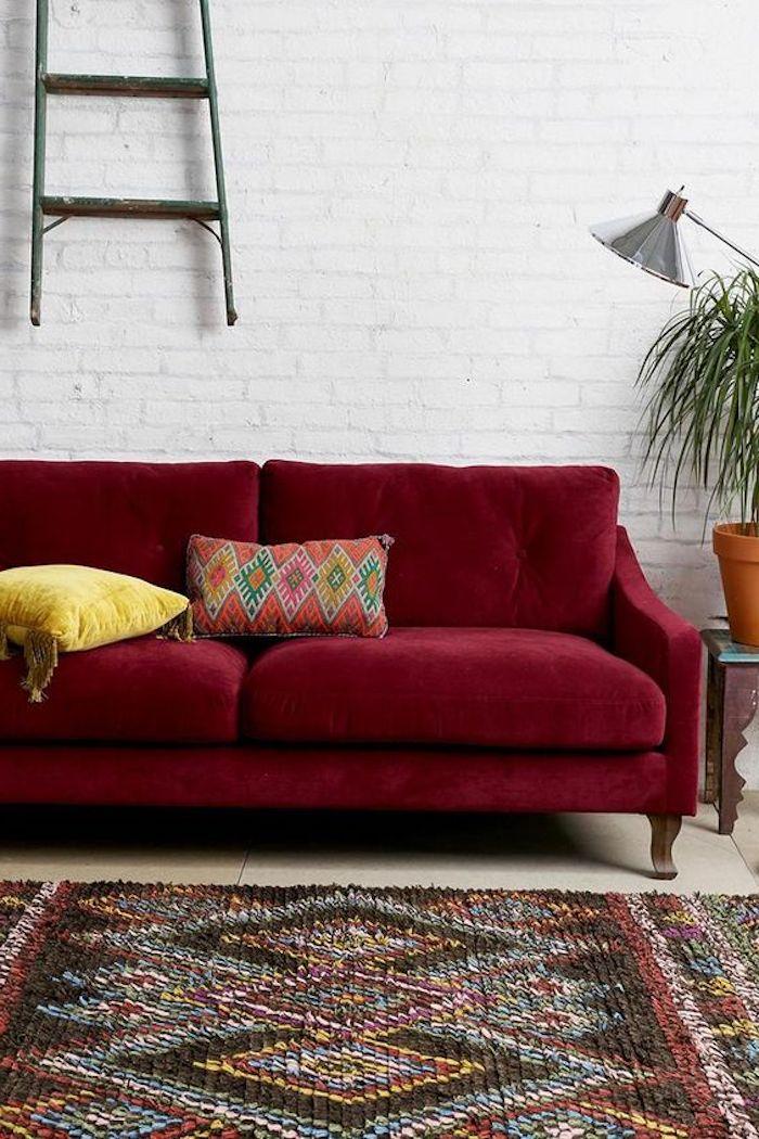 association de couleur, canapé bordeau sur un fond blanc, mur en briques, tapis coloré, échelle deco murale