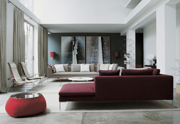 canapé couleur bordeau avec sol aspect béton, tapis blanc cassé, canapé gris, chaises originales, mur d accent gris, panneaux décoratifs, tables gigognes
