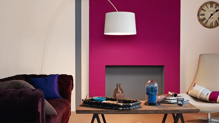 canapé couleur bordeau et pan de mur cheminée couleur framboise, table en bois rustique, fauteuil pivotant blanc