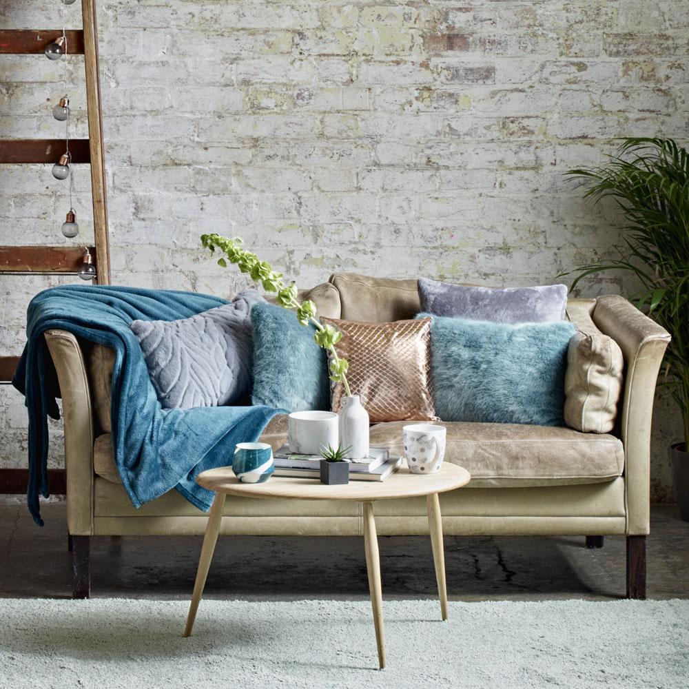 association couleur beige canapé, paré de coussins rose, bleu et mauve, couverture bleue, tapis gris, mur blanc défraichie