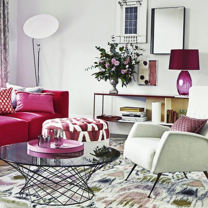 idée de canapé et autres accents couelur framboise, table basse en verre, tapis coloré, fauteuil blanc, petit étagère de rangement