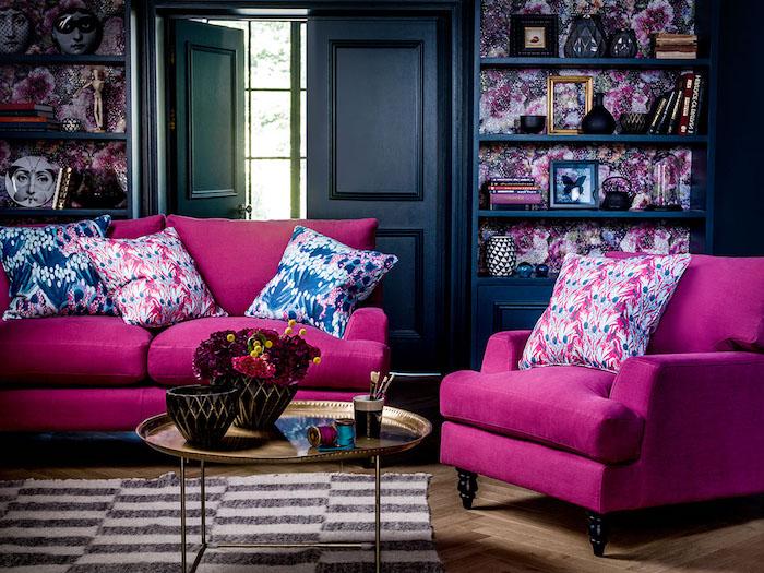 idée de canapé et fauteuil couleur framboise dans un salon bleu marine foncé, tapis zèbre, table basse orientale dorée, bibliothèque bleue, accessoires déco insolites