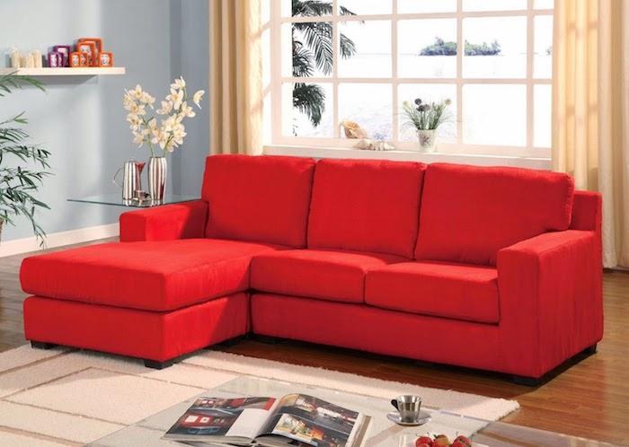 canapé rouge vermillon dans un salon neutre, tapis et rideaux couleur beige, mur couleur bleu clair, parquet marron, table basse en verre