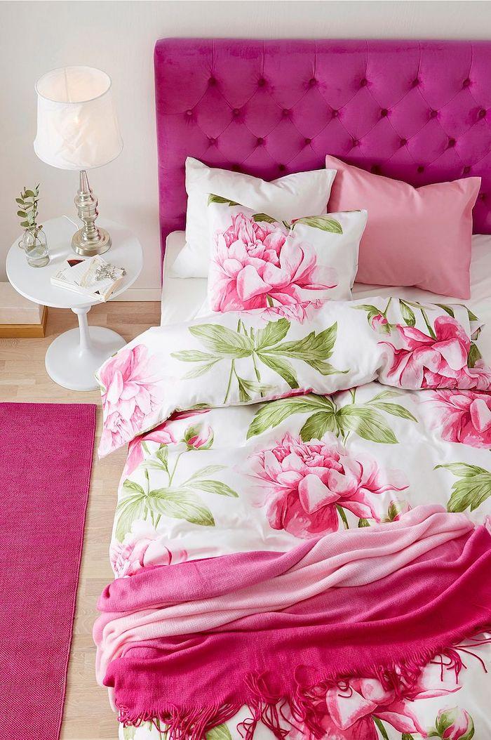 tête de lit, tapis et couverture couleur framboise, linge de lit blanc à imprimé fleuri, parquet clair, table de chevet blanche