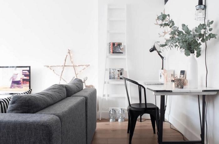 idée de salon scandinave blanc, canapé gris, parquet clair, table blanche avec chaise noire en metal, échelle blanche range magazines