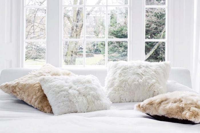 idée de coussin cocooning, des taies de coussin en fausse fourrure, linge de lit blanc, grandes fenêtres