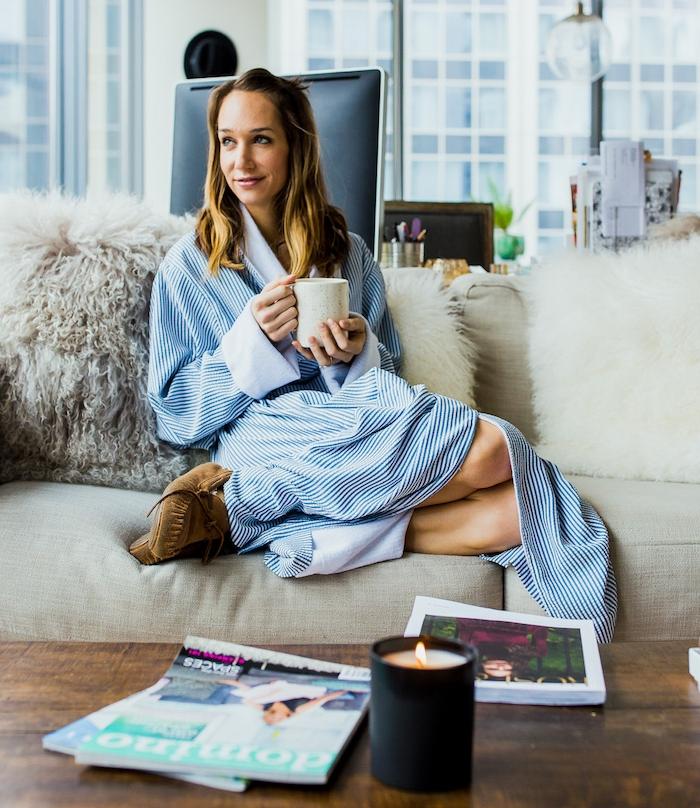 modele de deco cocooning dans un petit salon, table basse en bois marron, canapé gris clair, coussins blanches, jeté fausse fourrure, femme qui prend son café le matin