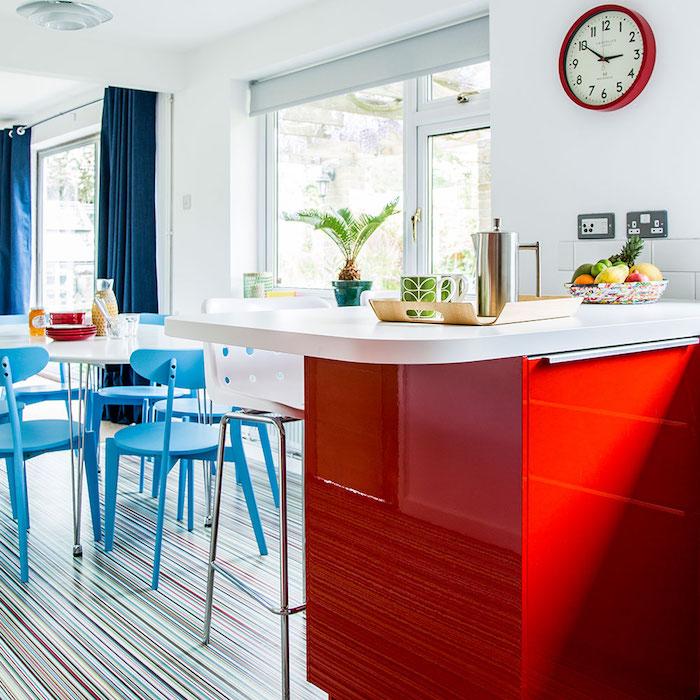 deco bleue et rouge dans une cuisine ouverte sur une salle à manger, ilot central rouge avec plan de travail blanc, table blanche et chaises bleues, fond blanc