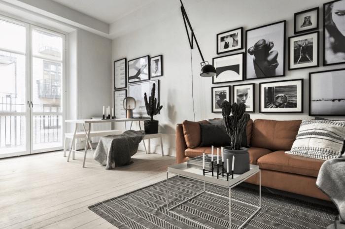 salon scandinave en noir et blanc graphique avec un canapé marron, tapis gris, parquet clair, coin repas banc en table blanche, deco murale photographie noir et blanc