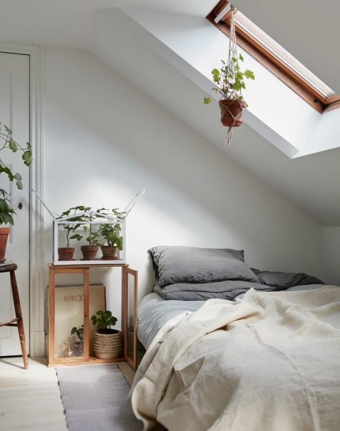 deco de chambre sous pente, linge de lit blanc et gris, tapis gris, parquet clair, decoration de plantes vertes, inspiration scandinave