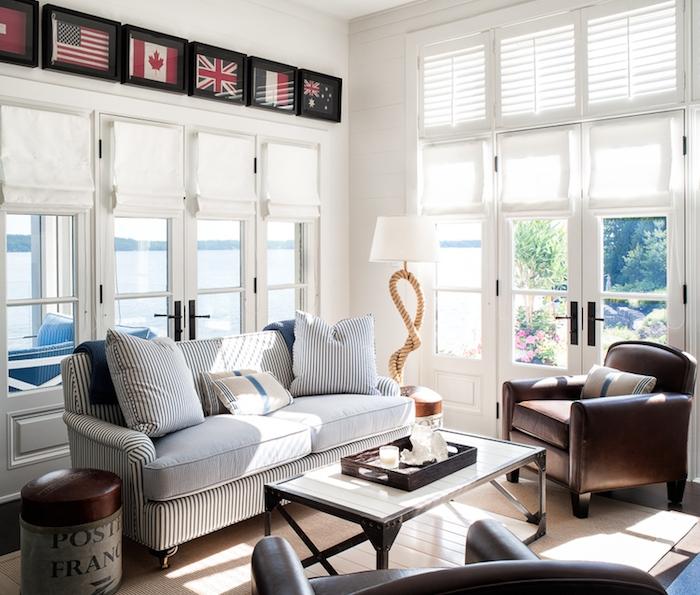 salon couleur blanc, avec canapé à rayures blanches, bleues t noires, table basse en bois et metal, fauteuils en cuir marron, association couleur beige en tapis