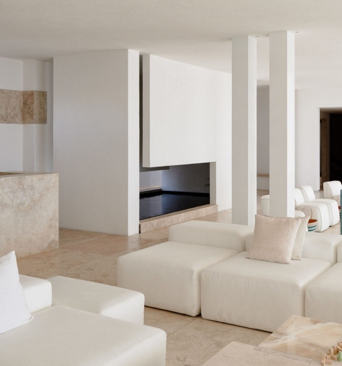 salon blanc et beige épuré, revêtement sol carrelage beige, façon marbre, canapés et fauteuils blancs, mur couleur blanche