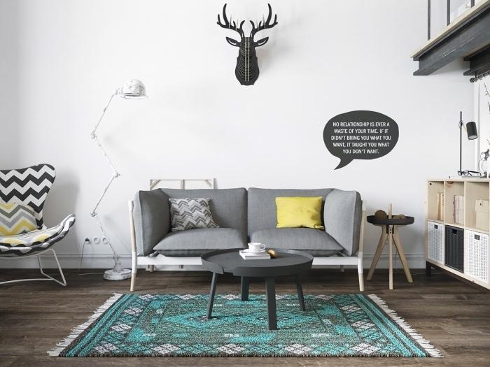 meuble scandinave, canapé et table basse gris, tapis gris et bleu, parquet marron, fauteuil blanc, gris et jaune, deco murale trophée de chasse