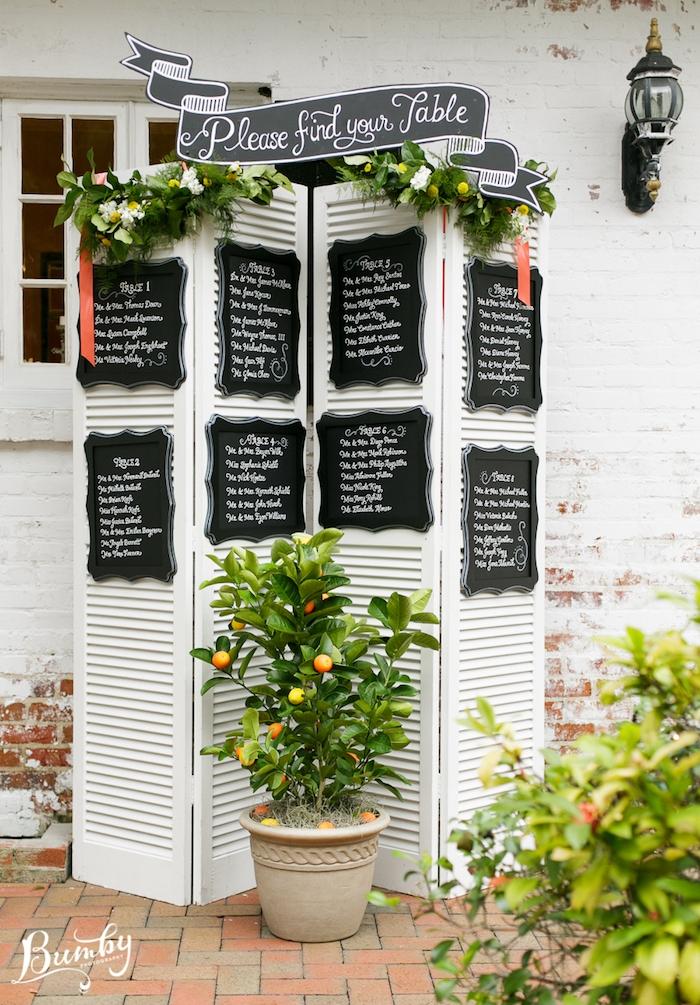 un paravent blanc avec des tableaux noirs, noms invités écrits en blanc, guirlande verte, oranger, mariage en plein air