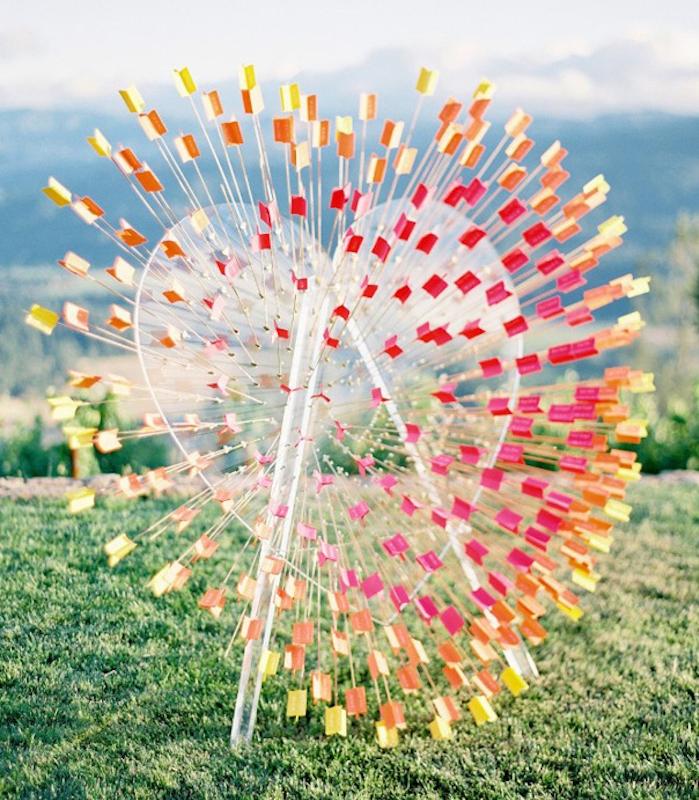 multiples flèches colorées qui passent à travers un grand coeur en plastique avec les noms des invités, plan de table mariage original