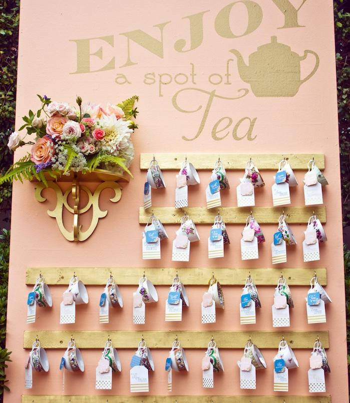 exemple de plan de table mariage, fond rose saumon, des tasses à thé suspendues avec bouquet de fleurs à côté, pause thé, petites étiquettes colorées