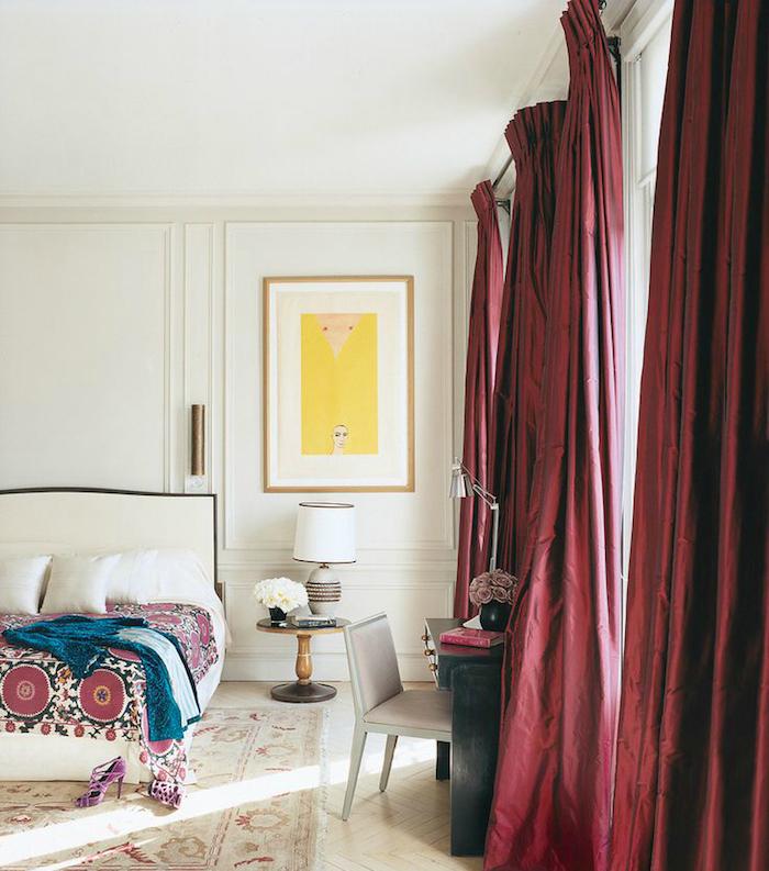 des rideaux couleur bordeau dans une chambre à coucher blanche, design, linge de lit blanc et couverture à motifs orientaux, tapis usé, parquet blanchi