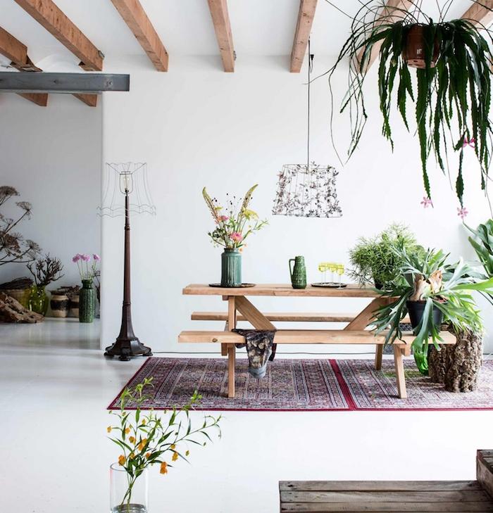 salle à manger deco cocooning, banc et table en bous, poutres apparentes, tapis oreintal, plantes vertes et fleurs