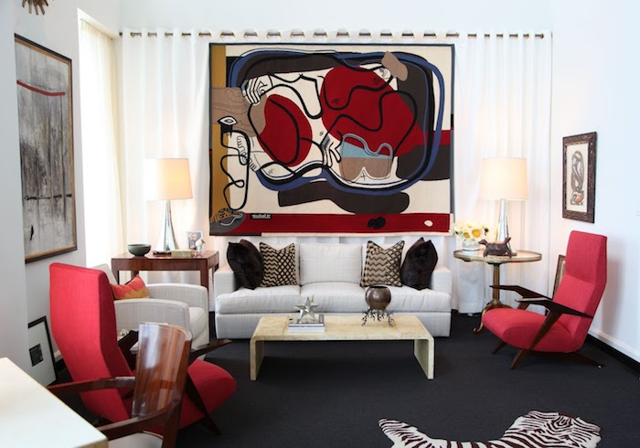 deco rouge et noir, tapis gris anthracite, fauteuils rouges, table basse en bois, canapé et fauteuil blanc cassé, tapis zèbre, deco murale cadre peinture abstraite