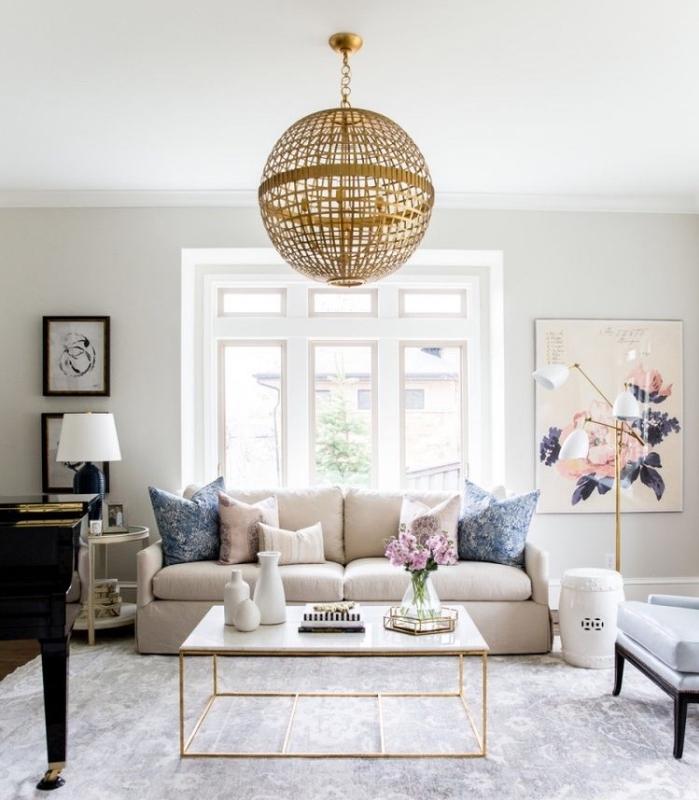 idee deco salon moderne en blanc et beige, tapis gris, canapé lin avec coussins beiges et bleus, suspension dorée, table basse marbre, deco murale peintures